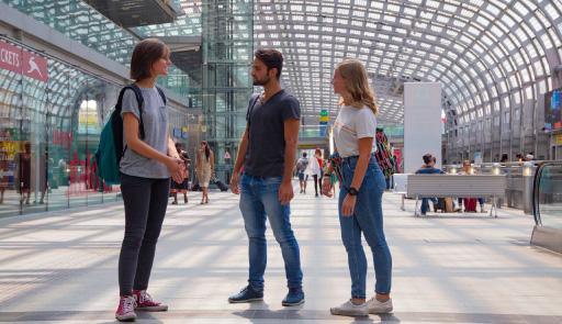 un ragazzo e due ragazze in una stazione ferroviaria