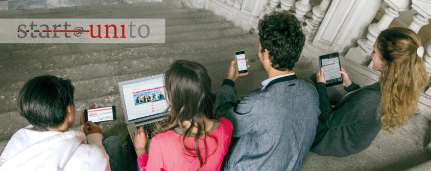 Foto di ragazzi seduti su una scalinata che consultano il tablet e il pc